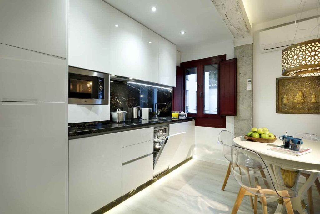 open kitchen with dishwasher and washing machine in new apartment for rent near alhambra spain