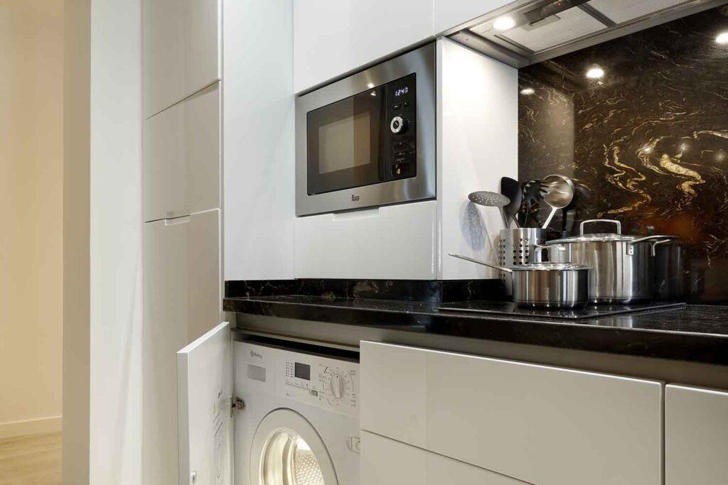 washer dryer machine in full kitchen of modern airbnb accommodation in albayzin, granada, spain