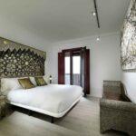 cozy bedroom with balcony overlooking the alhambra of granada, spain