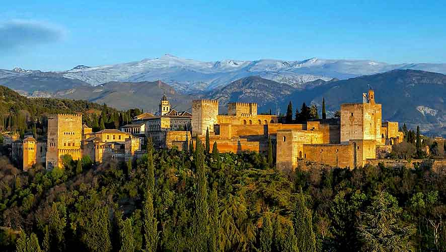 alhambra panoramic view at sunset against snowy mountains of Sierra Nevada spain