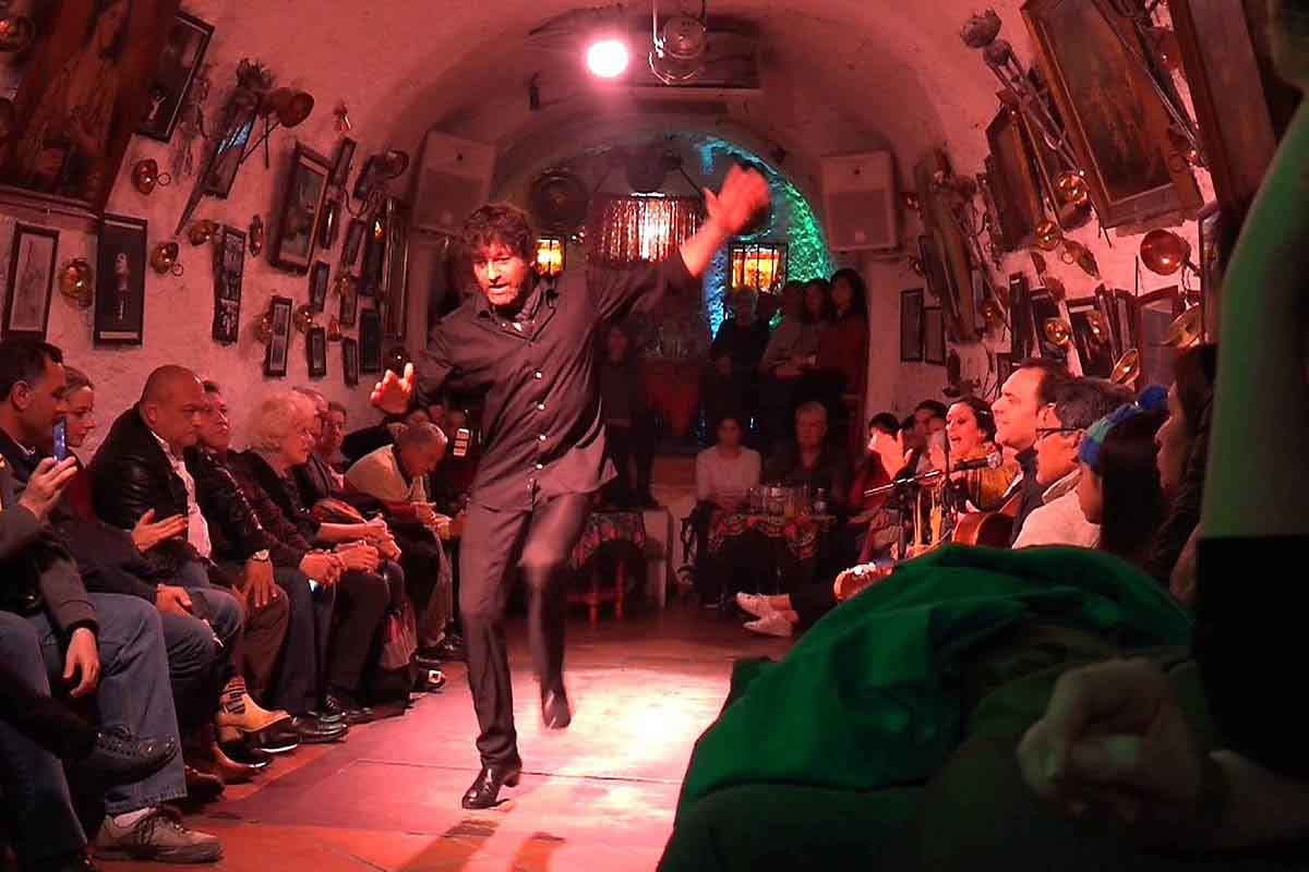 male flamenco dancer performing in a sacromonte cave under dimmed light, in granada