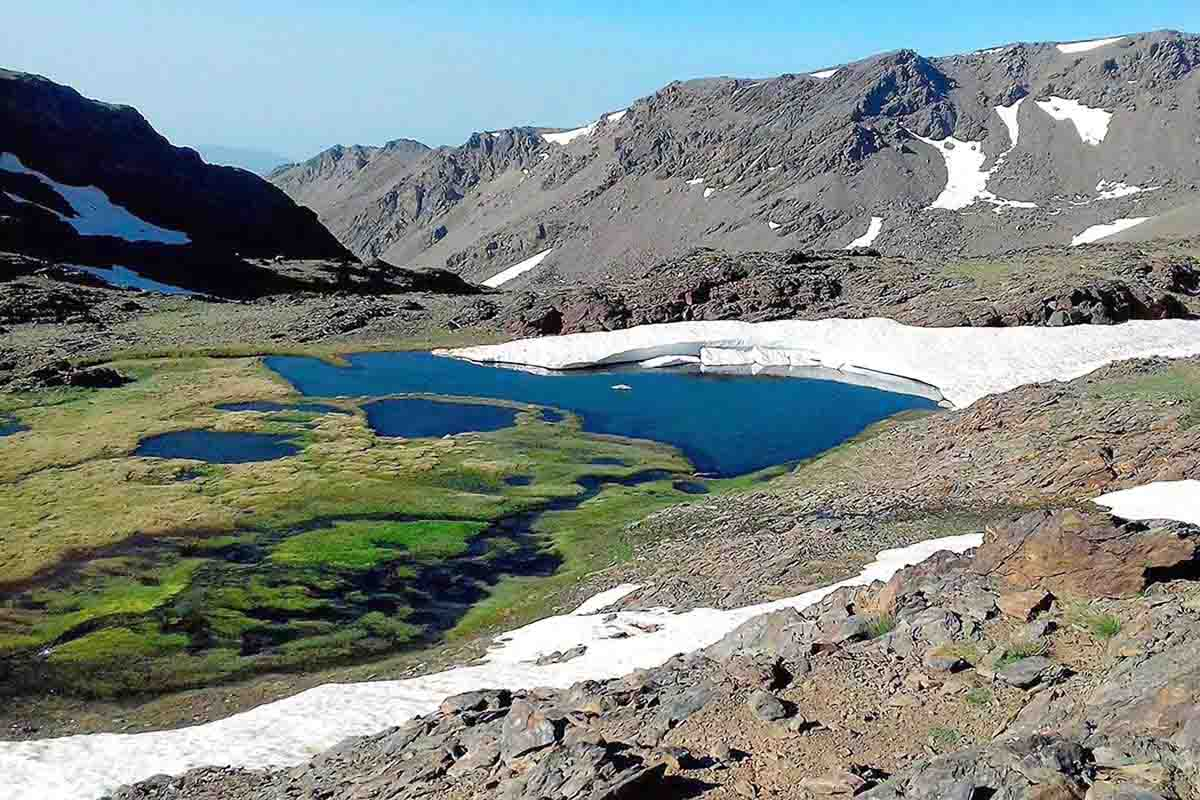 summer time at fresh water lagoon with thaw in Sierra Nevada mountains spain