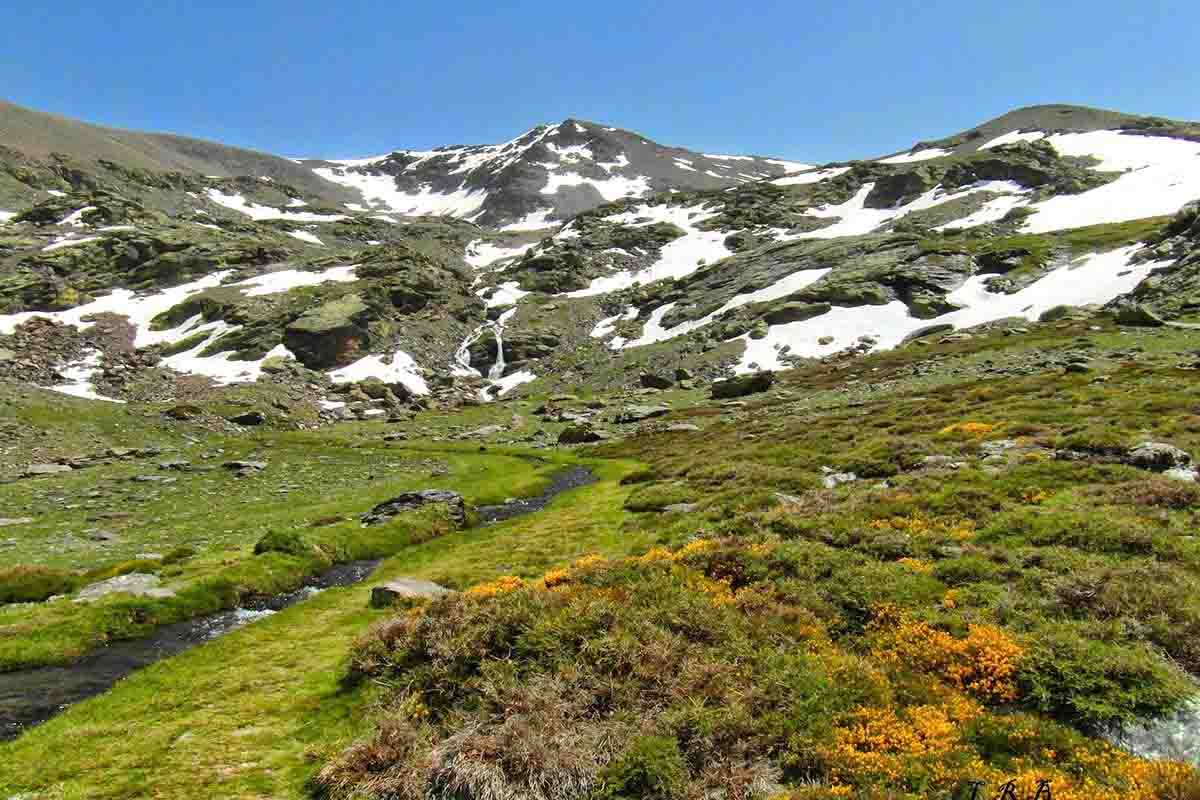 lush landscape with patches of snow in the Sierra Nevada summits, with Mulhacen in the background