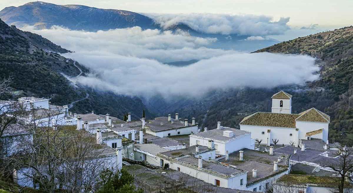 low clouds covering alpujarra village as the sun rises in distance, granada, spain
