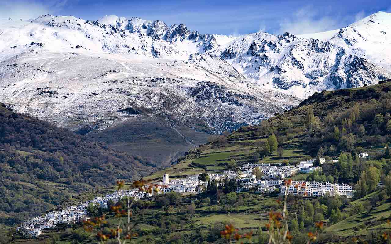 panoramic view of granada alpujarra town of Pampaneira with the snowed peaks of Sierra Nevada natural park in the back