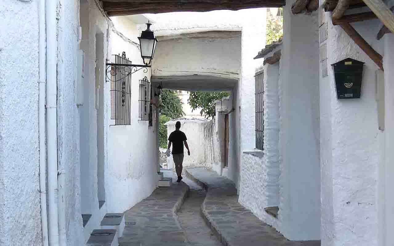 Pampaneira narrow street with white washed portico facades, granada
