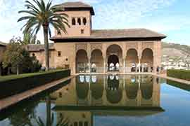 alhambra ticket partal with pond in foreground as part of tour guide visit to nasrid palaces, granada