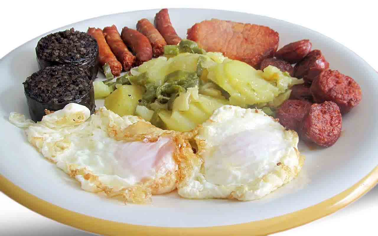 fried eggs, blood sausage, potatoes and meat in a alpujareno dish served in alpujarra de granada