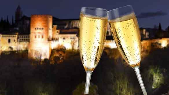 two Champaign glasses toasting against the alhambra fortress at sunset in the background, in Granada Spain