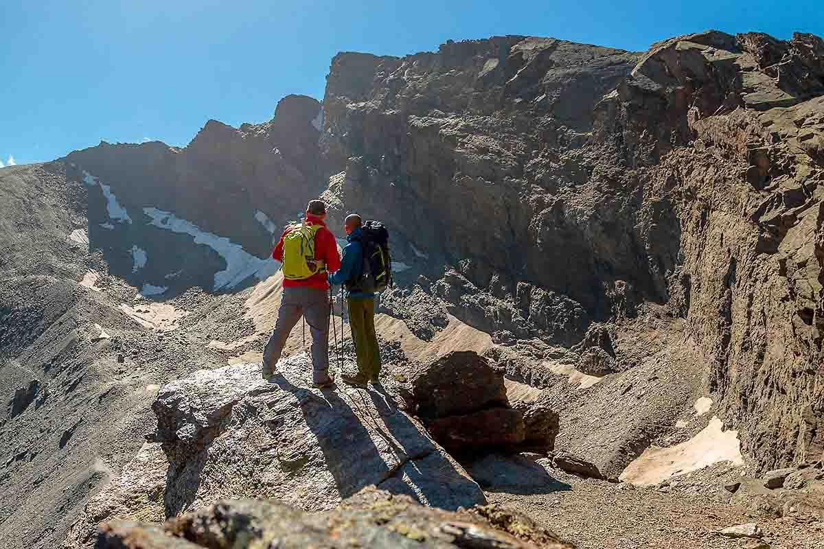 hikers watch a panoramic of Veleta peak with 200 meters fall on its north side, Sierra Nevada, spain